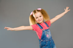 Little girl wearing jeans overalls Stock Photos