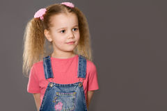 Little girl wearing jeans overalls Stock Photo