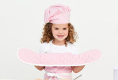 Little girl wearing kitchen gloves Stock Photo
