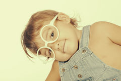 Little girl wearing overall and white glasses looking at camera Stock Images