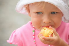 Little girl wearing panama hat is eating orange Royalty Free Stock Photos