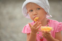 Little girl wearing panama hat is eating orange royalty free stock photography