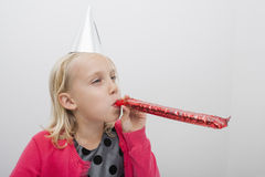Little girl wearing party hat blowing noisemaker at home Royalty Free Stock Photography