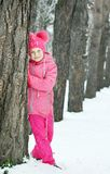 Little girl wearing pink clothes leaned against a pine tree trunk outdoors in winter Royalty Free Stock Images