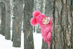 Little girl wearing pink clothes looks out from a pine tree trunk outdoors in winter Royalty Free Stock Photo