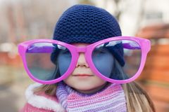 Little girl wearing a pink colored glasses Royalty Free Stock Photos