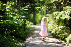 Little girl wearing pink dress taking a walk all alone Stock Images
