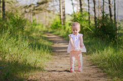 Little girl wearing pink dress taking a walk all alone in a park or forest Stock Images