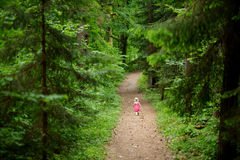 Little girl wearing pink dress walking all alone Stock Image