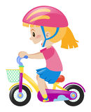 Little girl wearing pink helmet riding bike Stock Images