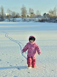 Little girl wearing a pink  and red  playing and running in a beautiful snowy winter field Royalty Free Stock Images