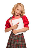 Little girl wearing plaid dress holding copy-book and pencils Royalty Free Stock Photo