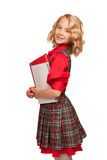 Little girl wearing plaid dress holding copy-book and pencils Stock Images