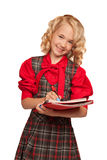 Little girl wearing plaid dress holding copy-book and pencils Stock Photo