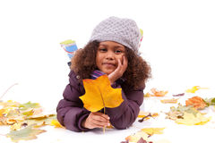 Little girl wearing playing with leaf trees Royalty Free Stock Images