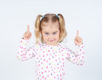 Little girl wearing  pointing by forefinger to somewhere up. Isolated Royalty Free Stock Photography