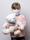 Little girl  wearing a protective mask. Little girl with teddy bear wearing a protective mask Stock Images