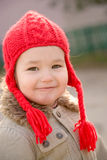 Little girl wearing a red hand knitted hat Stock Photography
