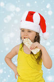 Little girl. Wearing red Santa hat eating chocolate Royalty Free Stock Photos