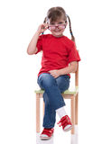 Little girl wearing red t-shirt and glass posing on chair. Isolated on white Stock Photo