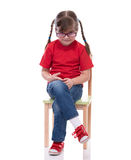 Little girl wearing red t-shirt and glass posing on chair Stock Images