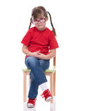 Little girl wearing red t-shirt and glass posing on chair Royalty Free Stock Photography