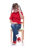 Little girl wearing red t-shirt and glass posing on chair Royalty Free Stock Photos