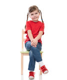 Little girl wearing red t-shirt and posing on chair Royalty Free Stock Images