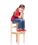 Little girl wearing red t-shirt and posing on chair Stock Image