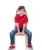 Little girl wearing red t-shirt and posing on chair Royalty Free Stock Image