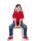 Little girl wearing red t-shirt and posing on chair. Isolated on white Royalty Free Stock Image