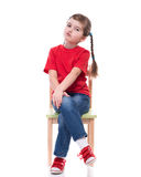 Little girl wearing red t-shirt and posing on chair Stock Photo