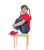 Little girl wearing red t-shirt and posing on chair Stock Images