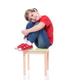 Little girl wearing red t-shirt and posing on chair Stock Photography