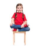 Little girl wearing red t-short and posing on chair. On white background Stock Image
