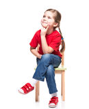 Little girl wearing red t-short and posing on chair Royalty Free Stock Photos