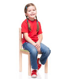 Little girl wearing red t-short and posing on chair. On white background Royalty Free Stock Photography