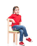 Little girl wearing red t-short and posing on chair. On white background Stock Photography