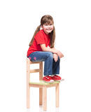 Little girl wearing red t-short and posing on chair. On white background Stock Images