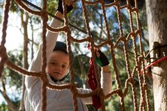 Little girl wearing safety harness climbing rope fence. In the forest Stock Images