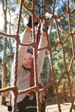Little girl wearing safety harness climbing rope fence. In the forest Stock Photo