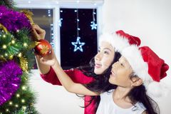 Little girl decorates Christmas tree with her mother Royalty Free Stock Images