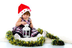 Little girl wearing a Santa hat. And playing with baubles.  on white background Stock Photography