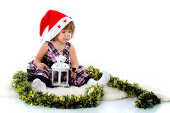 Little girl wearing a Santa hat. And playing with baubles. Isolated on white background Royalty Free Stock Photos