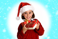 Little girl wearing santa hat carrying many gift boxes. For Christmas on fantasy background Royalty Free Stock Image