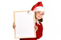 Little girl wearing santa hat holding blank board. For advertisementon on white background.    Invitation to christmas activities. Winter clothes Stock Images