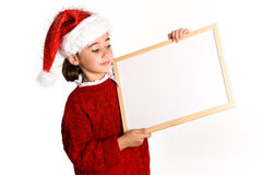 Little girl wearing santa hat holding blank board. For advertisementon on white background.    Invitation to christmas activities. Winter clothes Royalty Free Stock Images