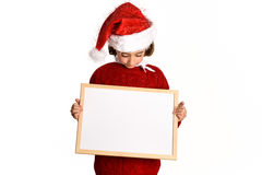 Little girl wearing santa hat holding blank board. For advertisementon on white background.    Invitation to christmas activities. Winter clothes Royalty Free Stock Photography