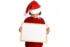 Little girl wearing santa hat holding blank board Royalty Free Stock Photography