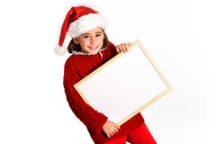 Little girl wearing santa hat holding blank board Royalty Free Stock Images